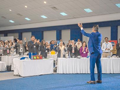 Man in blue suit speaking to audience