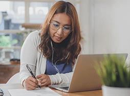 Woman taking notes while watching laptop