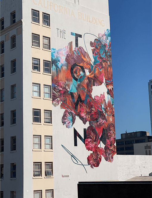 """This artwork is called """"The Town"""" and is painted on a building in Oakland, California."""