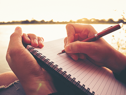 Hand holding pen writing in journal
