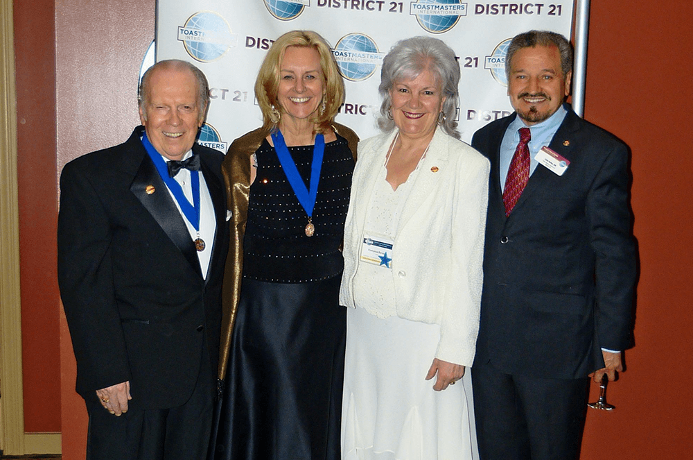 Page poses with Past District Governors from District 21 at a Toastmasters event.