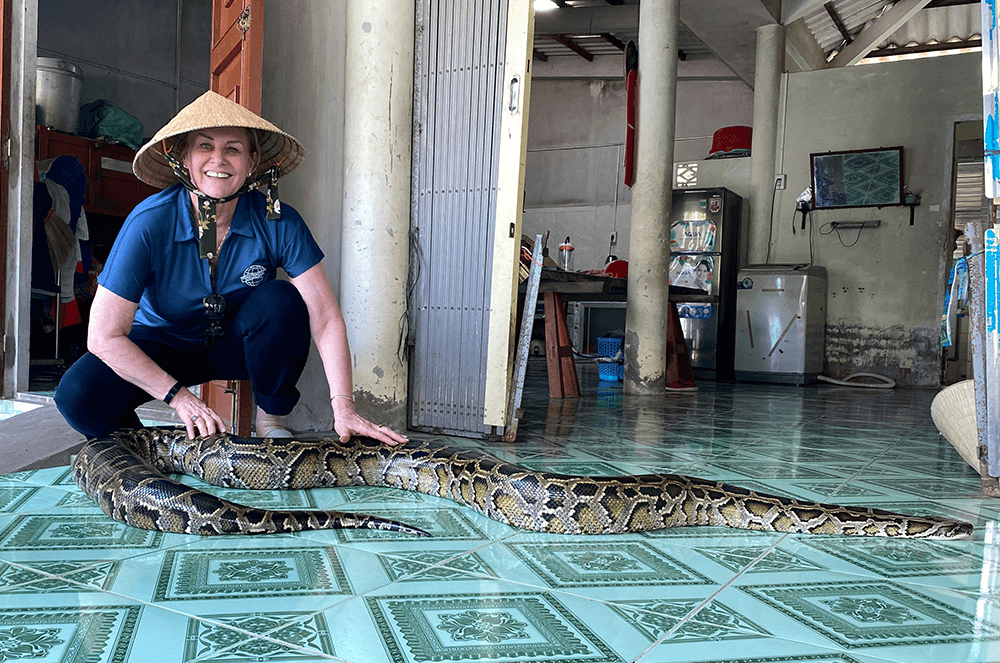 Margaret Page, DTM, greets a snake in Vietnam during Mid-year Training in 2019.