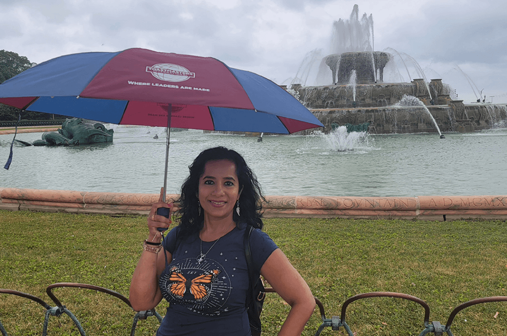 Deepa Venkat, DTM, of Frisco, Texas, shows her Toastmasters pride while staying dry at the Buckingham Fountain in the center of Grant Park in Chicago, Illinois.