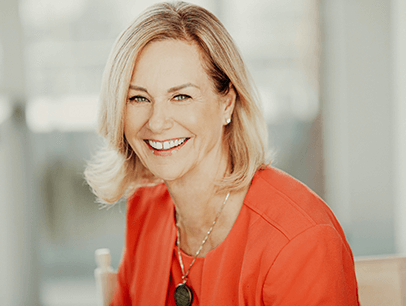 Margaret Page smiling in orange jacket