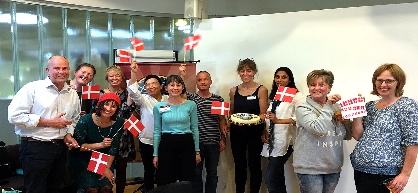 Toastmasters in Fredensborg, Denmark, celebrate the club's 6th anniversary in traditional Danish style with flags and cake.