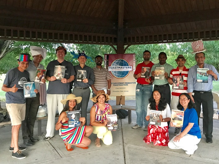Members of State Street Princeton Toastmasters  club in Plainsboro, New Jersey, celebrate the end of summer with an outdoor meeting, some silly hats, and their Toastmaster magazines.