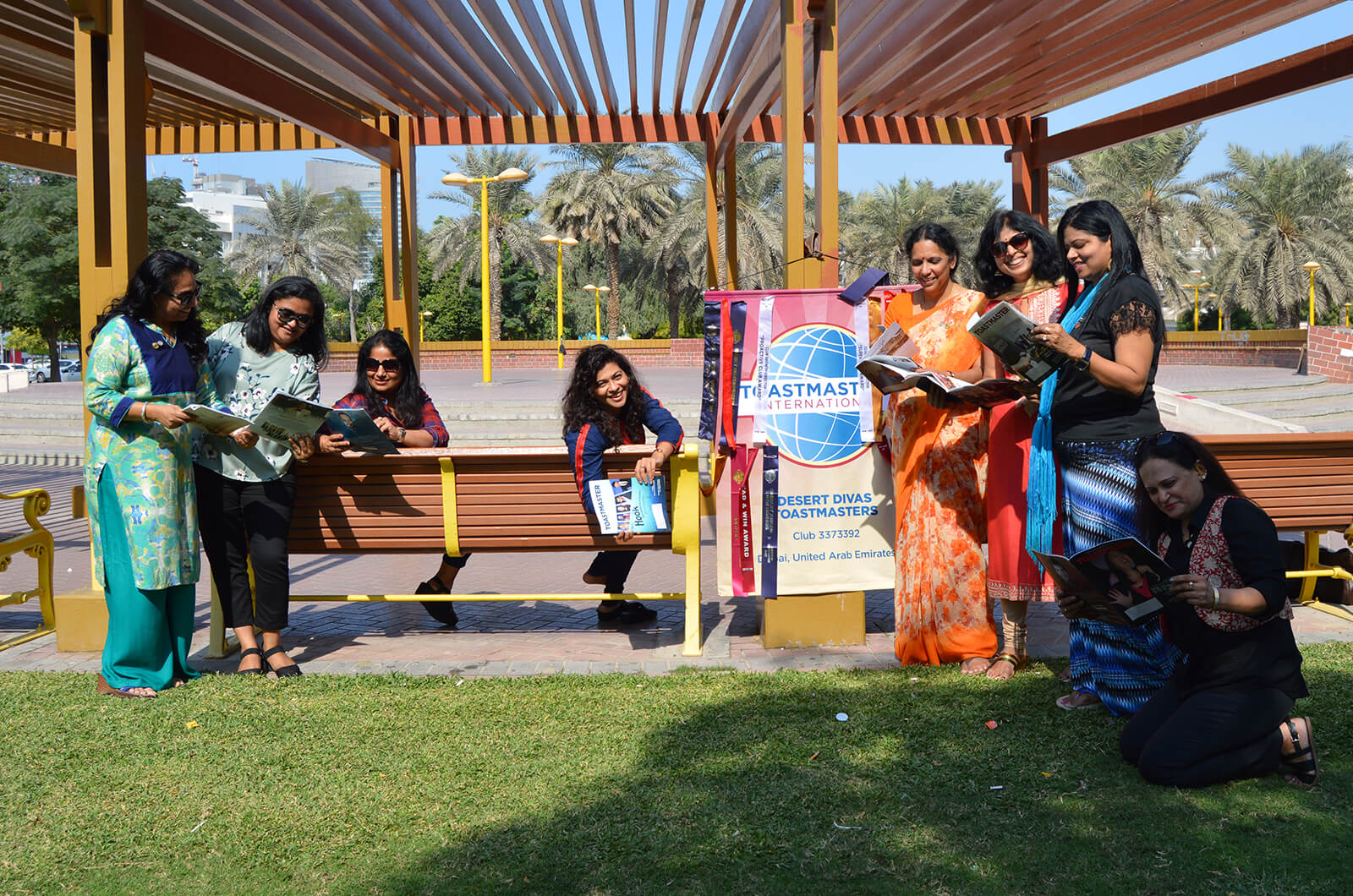 Members of the Desert Divas club of Dubai, United Arab Emirates, relax in the shade while hosting a meeting at a local park.