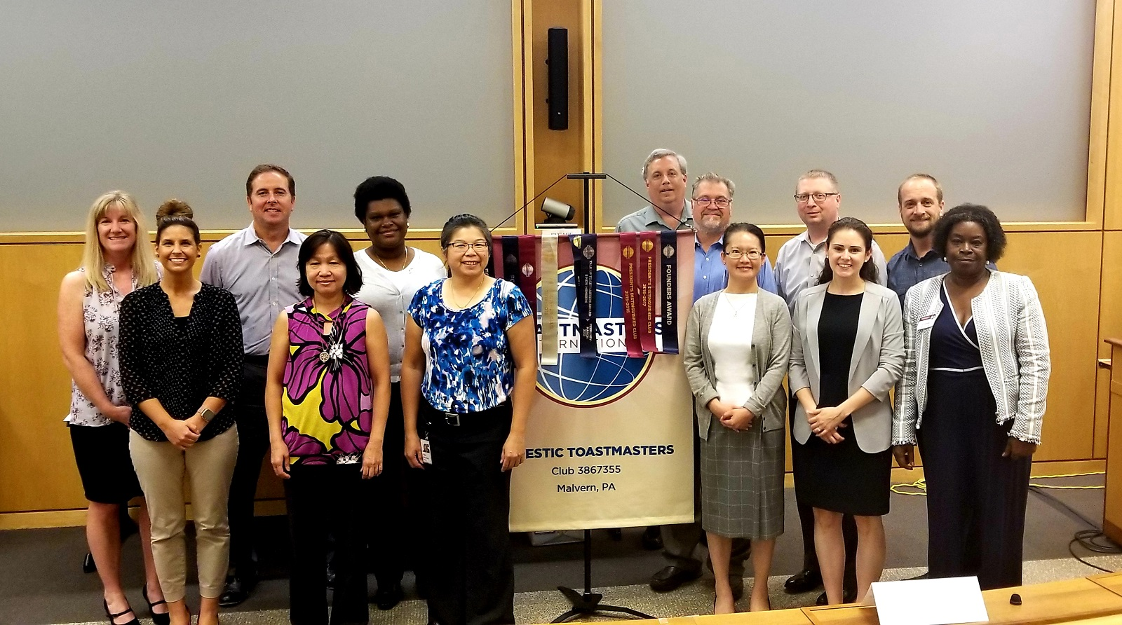The diverse members of the Majestic Toastmasters club in Malvern, Pennsylvania, pose proudly with their club banner.